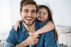 Портрет красивого отца и его милой дочери обнимая, смотря камеру и усмехаясь пока сидящ на софе дома стоковые фотографии rf