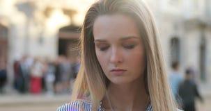 Портрет красивой белокурой девушки на улице looing вниз и после этого застекляя в камеру с ее большими яркими глазами акции видеоматериалы