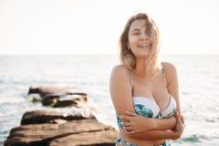 Портрет красивой усмехаясь молодой женщины в бикини на пляже Женская модель представляя в купальнике на береге моря Летние отпуск стоковые изображения rf