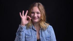 Портрет крупного плана взрослой кавказской женщины смотря камеру усмехаясь и показывая жестами handsign одобряет акции видеоматериалы