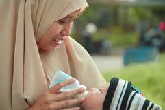 Портрет крупного плана красивого питьевого молока ребенка от его матери от питаясь бутылки стоковая фотография rf