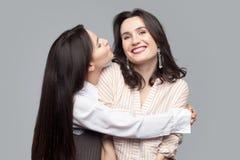Портрет крупного плана красивой длинной с волосами девушки брюнета обнимая и попробовать поцеловать ее лучший друг или сестру и д стоковые фотографии rf
