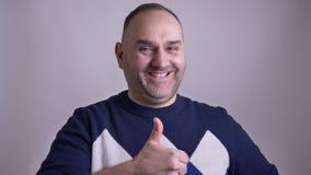 Портрет крупного плана мужчины достигшего возраста серединой кавказского показывая большой палец руки вверх и усмехаясь и делая г видеоматериал