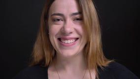Портрет крупного плана молодой жизнерадостной кавказской женщины усмехаясь и смеясь счастливо пока смотрящ камеру st с предпосылк видеоматериал