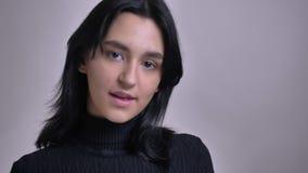 Портрет крупного плана молодой привлекательной кавказской женской модели представляя перед камерой и усмехаться акции видеоматериалы