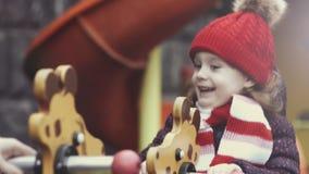 Портрет крупного плана счастливого смеясь возраста 3-4 девушки в теплых одеждах играя на коромысле на яркой красочной спортивной  сток-видео