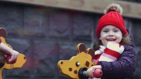 Портрет крупного плана счастливого смеясь возраста 3-4 девушки в теплых одеждах играя на коромысле на яркой красочной спортивной  акции видеоматериалы