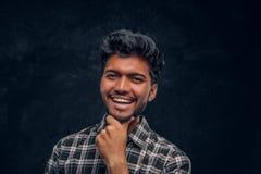 Портрет конца-вверх красивого индийского человека нося рубашку шотландки представляя с рукой на подбородке, усмехаясь и смотря стоковое изображение rf
