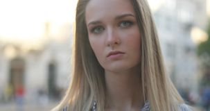 Портрет конца-вверх красивой блондинкы смотря камеру с лучами солнца на улице сток-видео