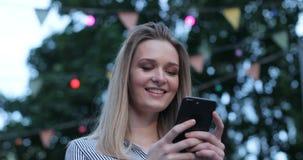 Портрет конца-вверх красивой кавказской девушки с яркими глазами печатая на ее сотовом телефоне и усмехаясь outdoors фронт видеоматериал