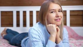 Портрет конца-вверх прелестной молодой усмехаясь женщины лежа на кровати в спальне и представлять сток-видео