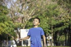 Портрет мальчика Азии смеясь и усмехаясь счастливо деревья предпосылки расплывчатые в парке стоковое фото rf