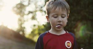 Портрет мальчика есть леденец на палочке outdoors видеоматериал