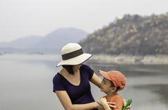 Портрет матери и сын усмехаясь горы и вода предпосылки на запруде Krasiew, Supanburi Таиланде стоковые изображения rf