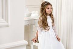 Портрет милой маленькой девочки на белых платье и венке на первых воротах церков предпосылки святого причастия стоковое изображение