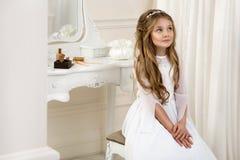 Портрет милой маленькой девочки на белых платье и венке на первых воротах церков предпосылки святого причастия стоковое фото