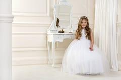 Портрет милой маленькой девочки на белых платье и венке на первых воротах церков предпосылки святого причастия стоковое фото rf