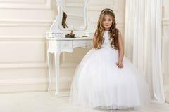 Портрет милой маленькой девочки на белых платье и венке на первых воротах церков предпосылки святого причастия стоковая фотография rf