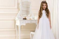Портрет милой маленькой девочки на белых платье и венке на первых воротах церков предпосылки святого причастия стоковое изображение rf