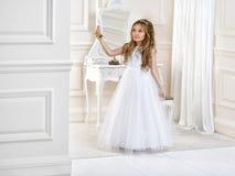 Портрет милой маленькой девочки на белых платье и венке на первых воротах церков предпосылки святого причастия стоковая фотография