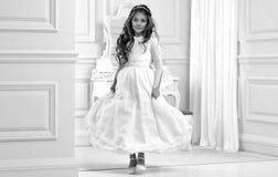 Портрет милой маленькой девочки на белых платье и венке на первых воротах церков предпосылки святого причастия стоковые изображения rf