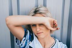 Портрет милой девушки с белым коротким стилем причесок Ее сторона крышки волос половинная Она смотрит вперед стоковое фото
