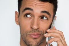 Портрет молодого красивого неуверенного человека используя мобильный телефон на серой предпосылке Бизнесмен смущает говорить по е стоковое фото rf