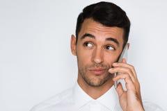 Портрет молодого неуверенного человека используя мобильный телефон на серой предпосылке Бизнесмен смущает говорить по его умному  стоковое изображение rf