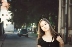 Портрет молодой красивой милой женщины с длинными волосами представляя в городе стоковая фотография