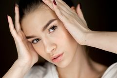 Портрет молодой красивой девушки коричнев-глаз с естественным макияжем держа ее руки на ее голове стоковое фото