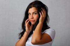 Портрет молодой, красивой девушки на серой предпосылке стоковое фото