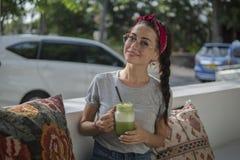 Портрет молодой темн-с волосами красоты с оплеткой ослабляя в на открытом воздухе кафе около дороги, брюнет в красной ветоши стоковое изображение