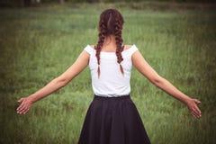 Портрет наслаждаться женщиной поднимая ее руки в поле стоковая фотография