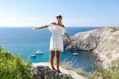 Портрет привлекательного женского человека в белых sundress против seascape стоковая фотография