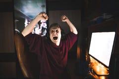 Портрет подростка gamer который выиграл компютерную игру и радуется с его поднятыми руками стоковые фотографии rf