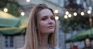 Портрет довольно романтичной девушки смотря в сторону и поворачивая ее сторону к камере Выравнивать света города на видеоматериал