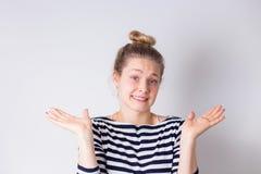 Портрет смущенной и расстроенной топорной милой и придурковатой женщины shrugging и рук распространения косых в безвыходном незна стоковая фотография
