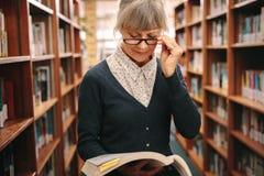 Портрет старшей женщины в eyeglasses читая книгу в libra стоковая фотография rf