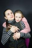 Портрет студии любящих матери и дочери, нежно и сильно обнимающ и держащ руки стоковые изображения rf