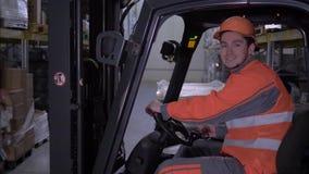 Портрет счастливого мужского водителя платформы грузоподъемника в трудных взглядах шлема и формы на камере и улыбках в складе видеоматериал