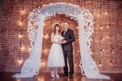 Портрет счастливого молодого жениха и невеста в классическом интерьере около свода свадьбы с цветками День свадьбы, тема любов fi стоковое фото