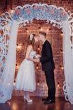 Портрет счастливого молодого жениха и невеста в классическом интерьере около свода свадьбы с цветками День свадьбы, тема любов fi стоковые фотографии rf