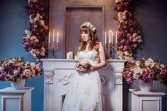 Портрет счастливой молодой невесты в классическом интерьере около камина с цветками День свадьбы, тема любов Первый день нового стоковые фото