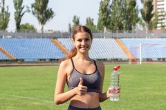 Портрет счастливой спортсменки держа бутылку воды и большого пальца руки вверх на стадионе Спорт и здоровая концепция стоковое фото rf