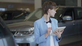 Портрет уверенной милой женщины в стильном костюме используя ее планшет проверяя автомобили в мотор-шоу Рассматривать дамы видеоматериал