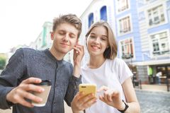 Портрет улицы счастливой молодой пары которая слушает музыку от одного наушника Улыбки девушки стоковая фотография