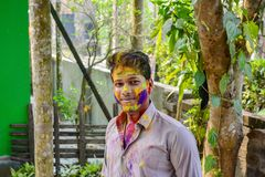Портрет усмехаясь подростка с красочной краской на стороне во время фестиваля holi в Индии стоковые фотографии rf