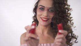 Портрет усмехаясь смешной молодой курчавой девушки смотря 2 halfs накаленных докрасна перцев chili движение медленное видеоматериал