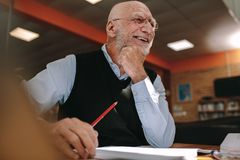 Портрет усмехаясь старшего человека сидя в библиотеке стоковое изображение rf