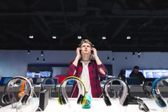 Портрет теста наушников человека в магазине пока слушающ музыку в наушниках стоковая фотография